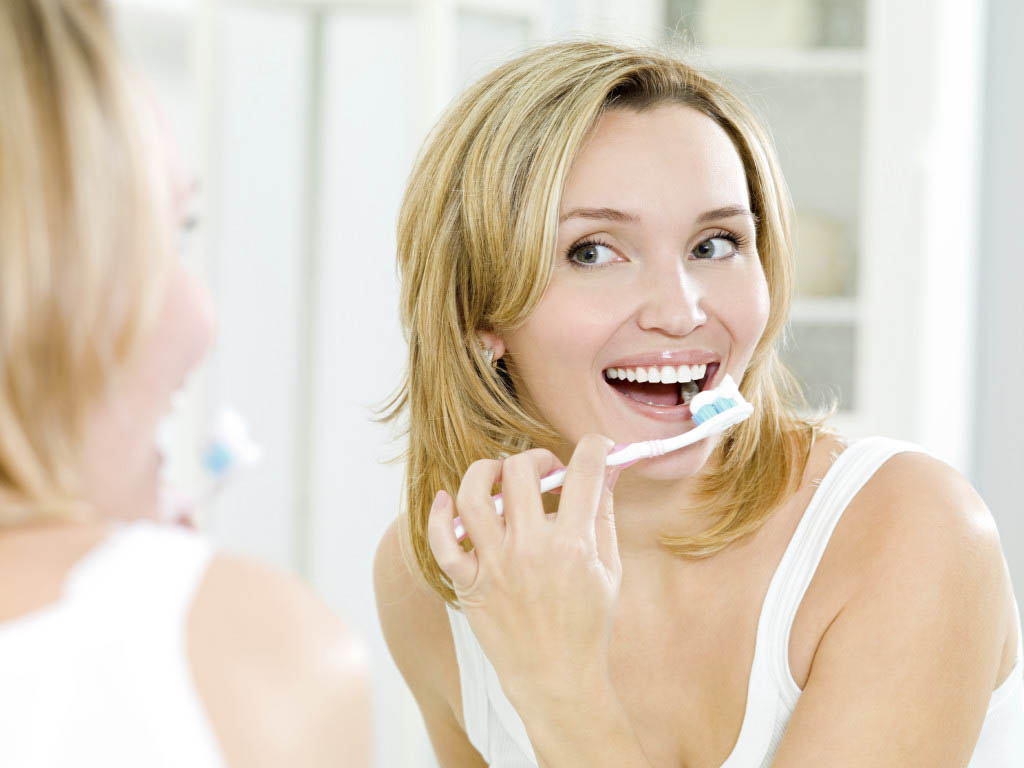 happy woman cleaning teeth with toothbrush